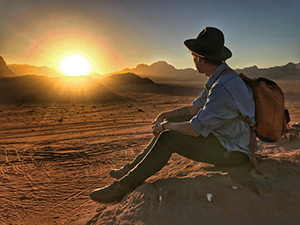 A person wearing a backpack and hat sitting on a rock watching the sun rise