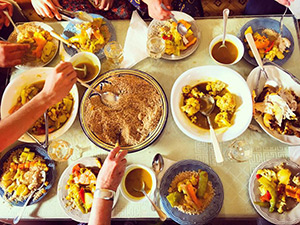 A shot of a table with many bowls and hands scooping the food