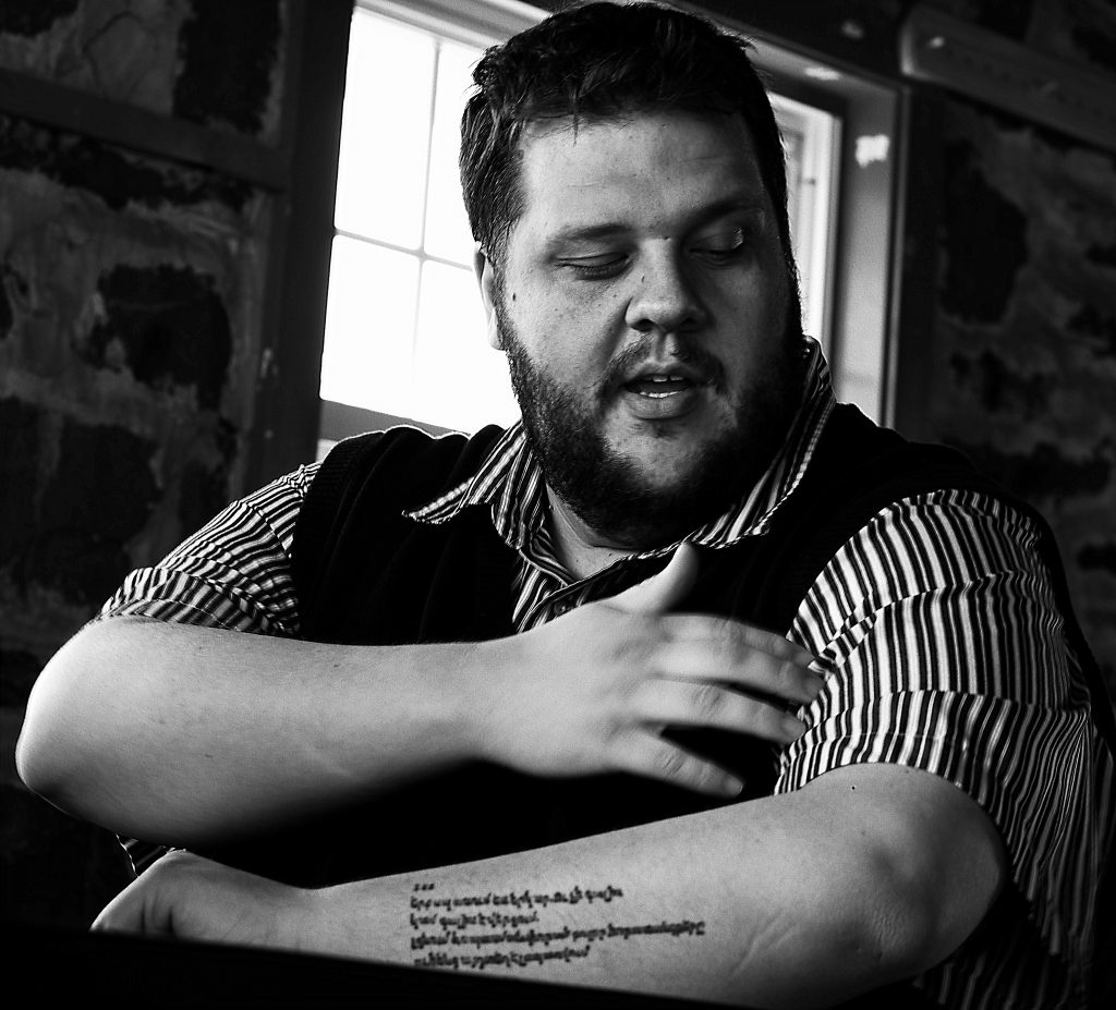 SIT alumnus and Peace Corps recruiter Adam Housh in black and white, displaying his tattooed forearm