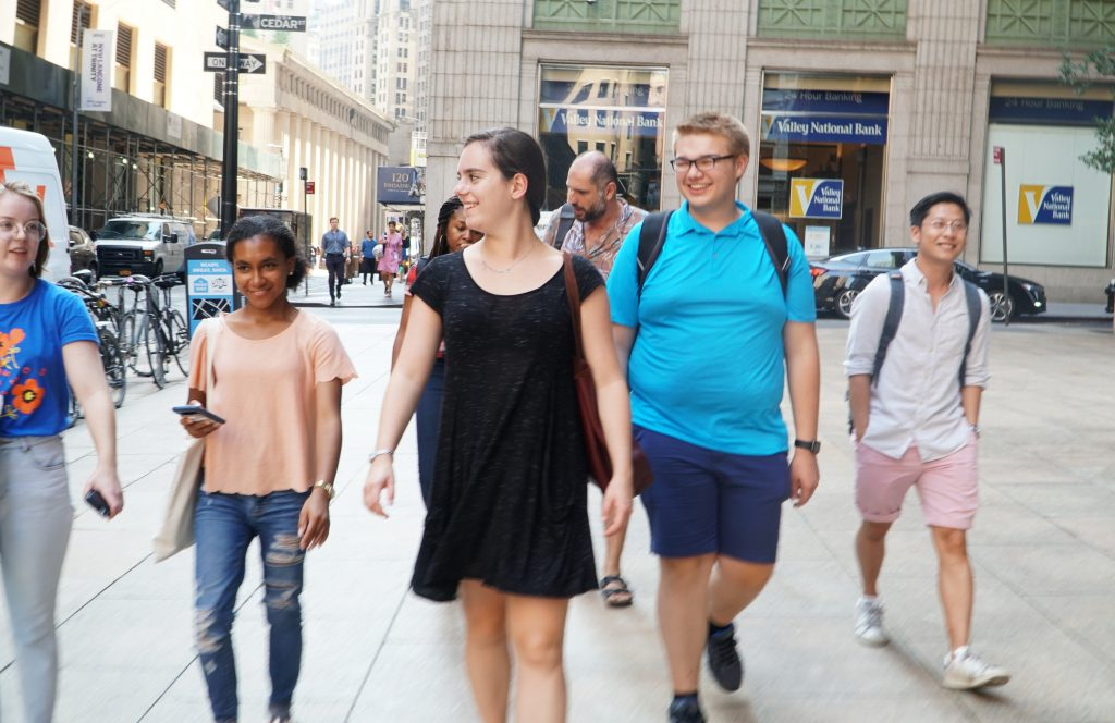 Five students walking on the sidewalk in NYC