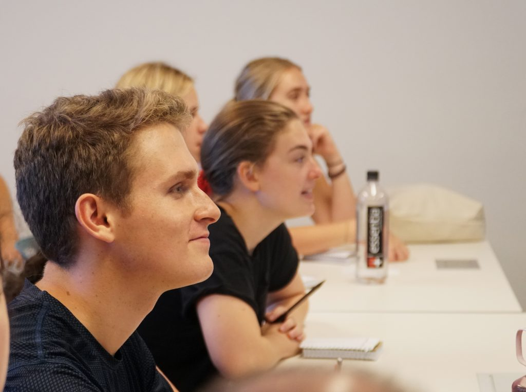 a smiling young male student sits at a table with three female students, listening to a presentation