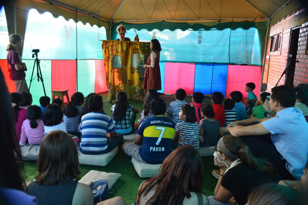 21 children sit on cushions on the floor and watch a puppet show