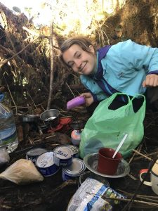 A young woman crouches and smiles near her camp supplies