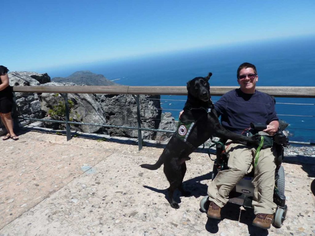 Alex Stone in his wheelchair in front of a railing on a high cliff beside the ocean in South Africa with service dog Fraser beside him
