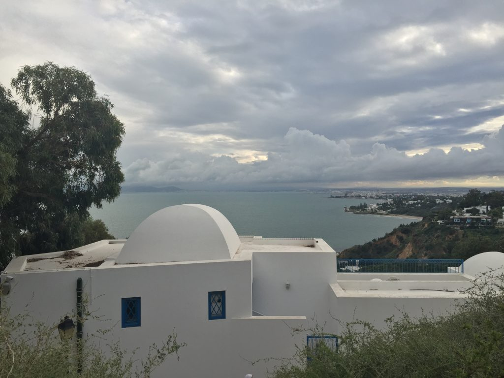 A white building in Sidi Bou Said, with the ocean behind it