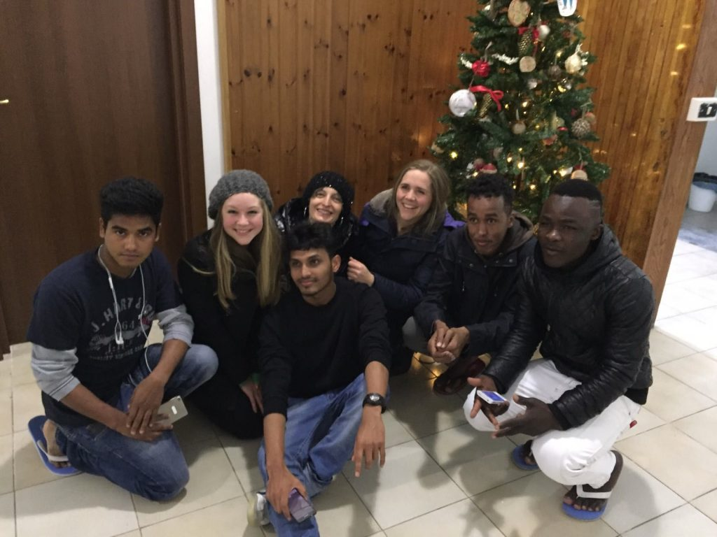 Seven people pose by a Christmas tree