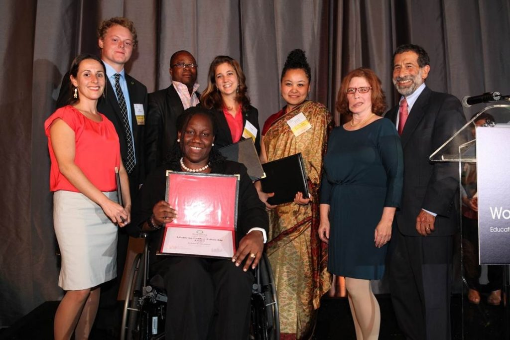 Komabu Pomeyie in wheelchair, holding her award, surrounded by seven people of varying genders, ethnicities, and ages