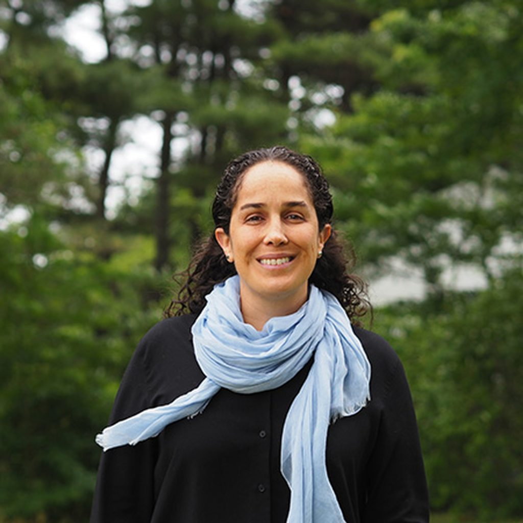 Smiling woman wearing scarf and standing in front of trees
