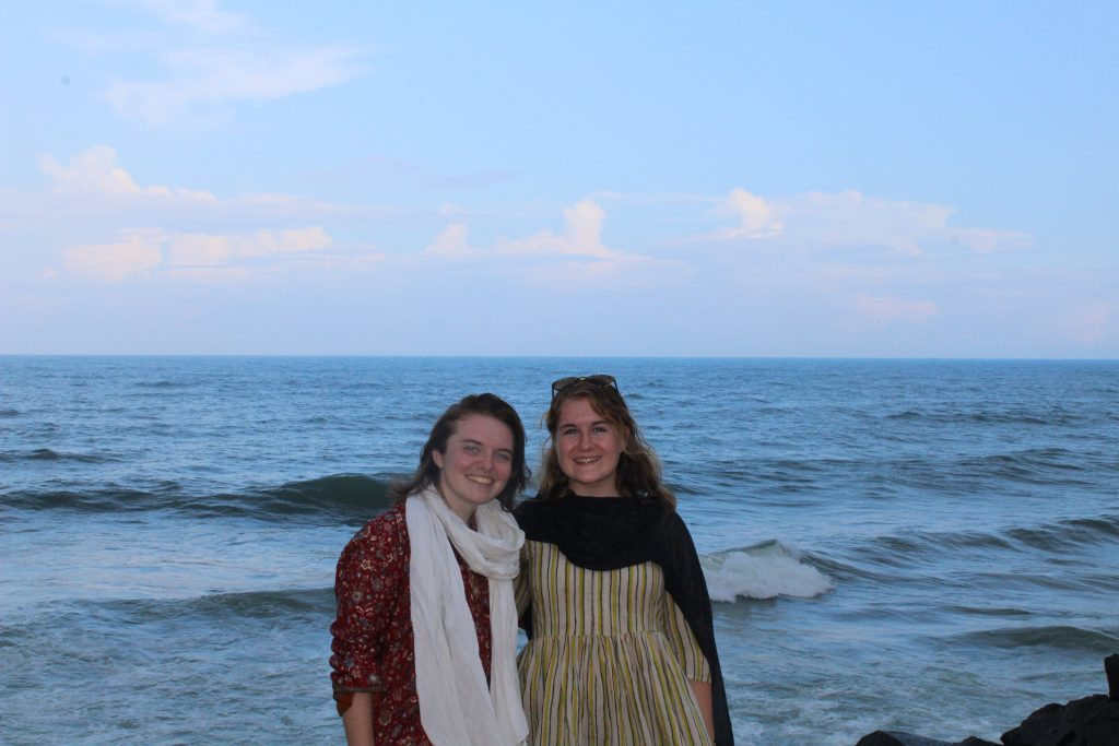 Two young women stand smiling in front of the ocean