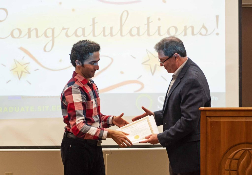 Male student receiving a handshake and certificate from his professor