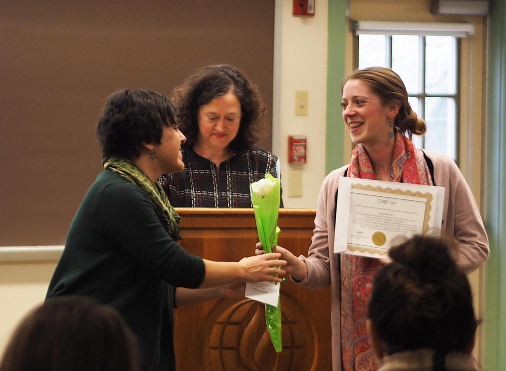 Female student smiles as she receives a rose from alumni director