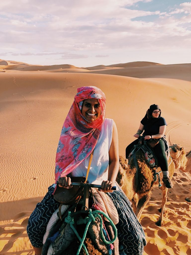 Two students riding camels in the desert