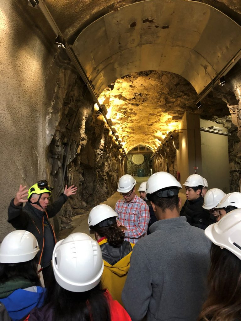 Students wearing white hardhats in  a tunnel listening to a man with arms open wide.