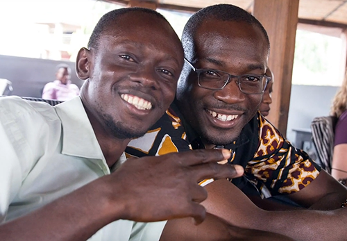 Kwabena and a young man smile at the camera