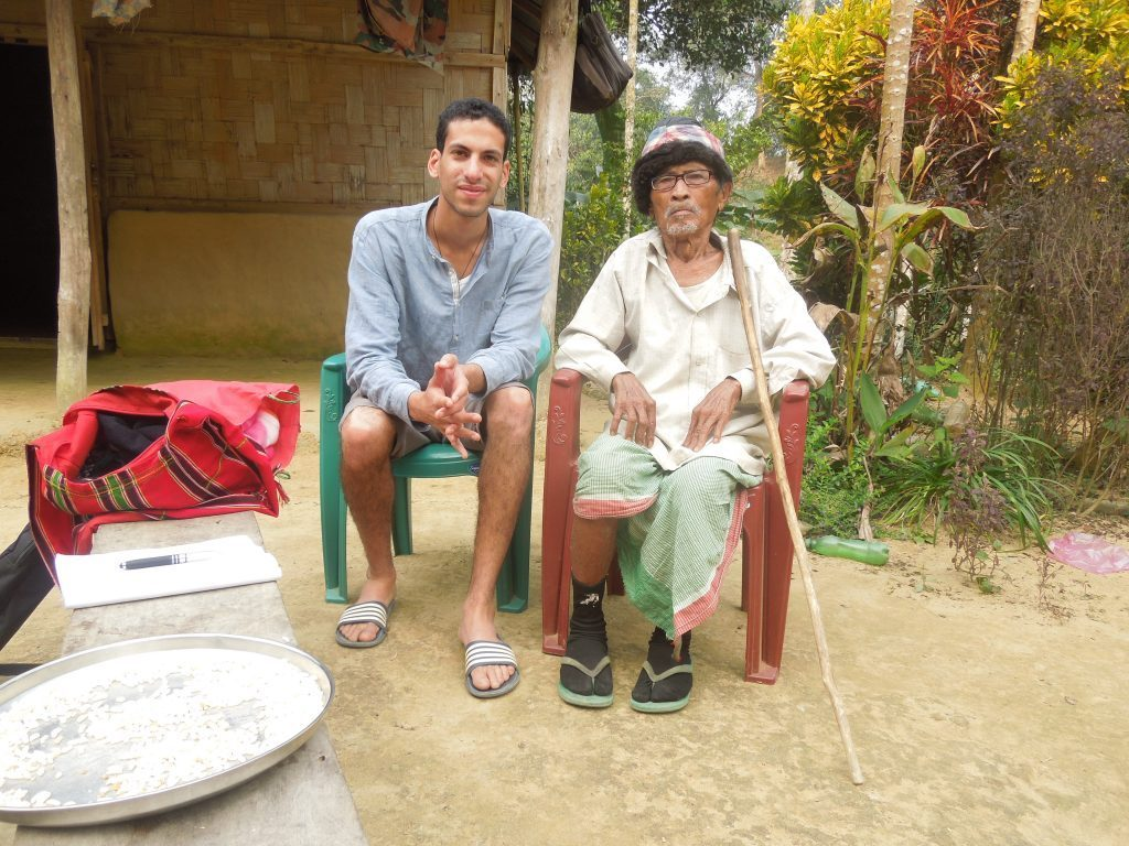 A young man sits with a village elder