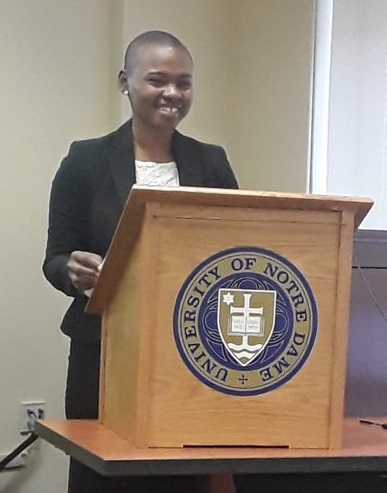 A young woman smiles at a lectern featuring the University of Notre Dame logo