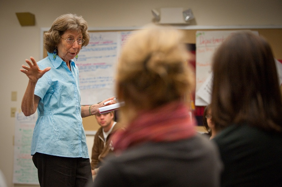 A woman speaks to a group of students