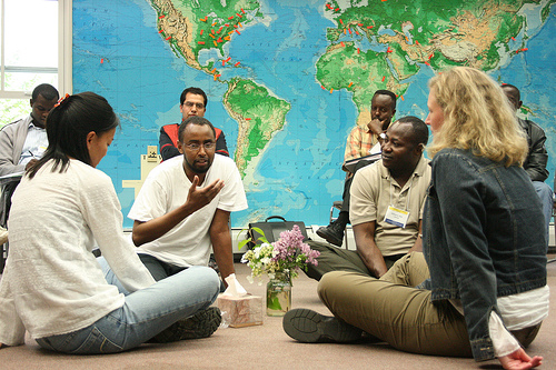 Four people sit in a circle on the floor with a world map in the background