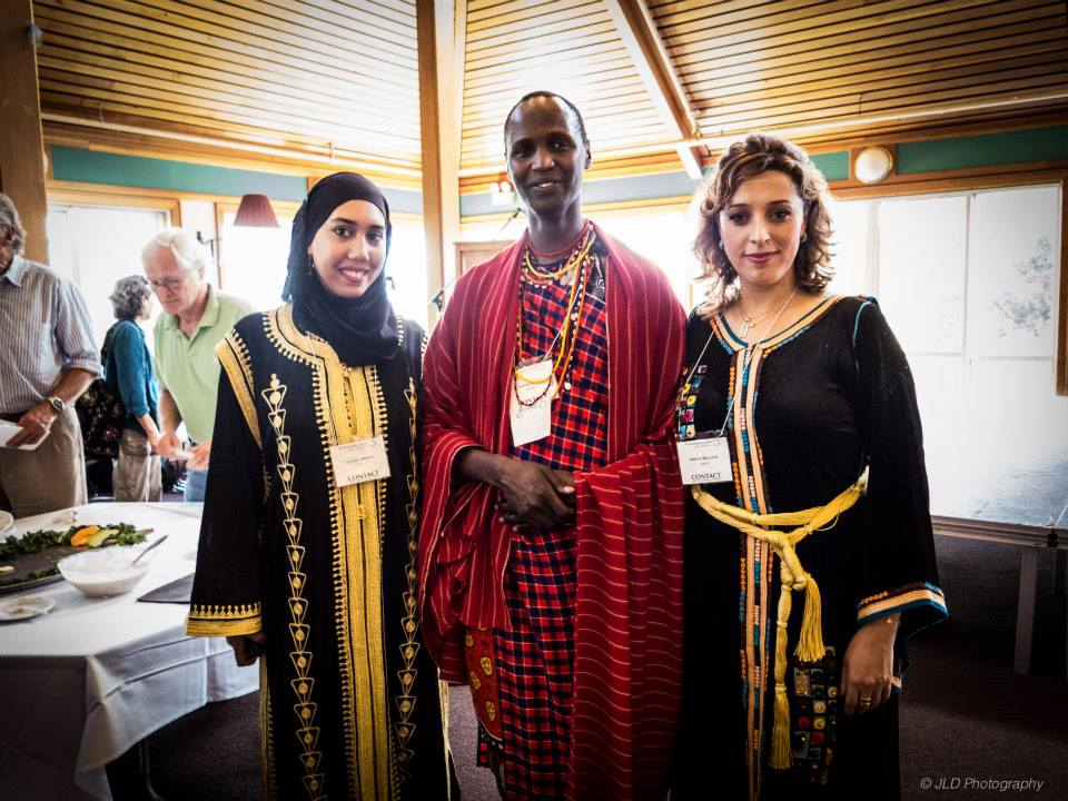 Three people face the camera wearing tunics and indigenous clothing