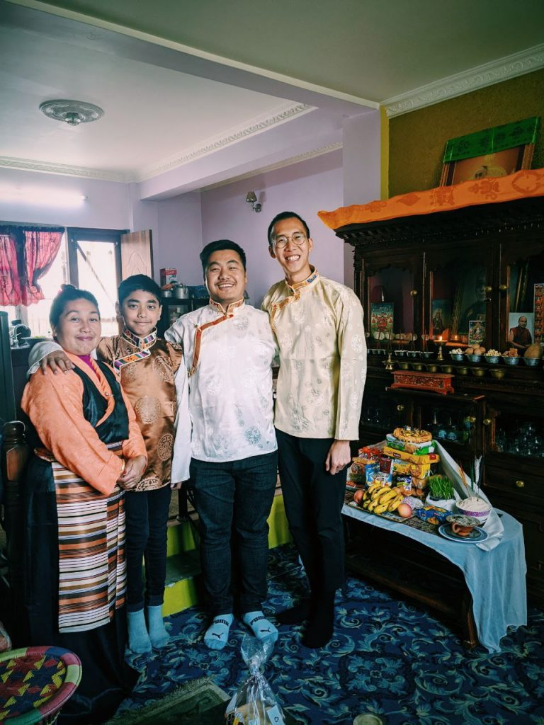 A family of three people and the study abroad student in a Nepali home