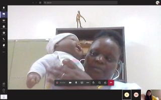 A screenshot of a woman using a baby doll to demonstrate how to perform a physical examination