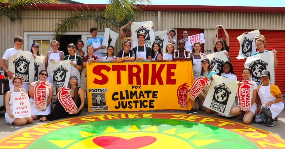 """A large group of students stand with posters and a large banner that says """"Strike for Climate Justice"""""""