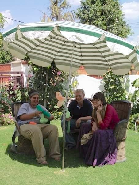 Three young adults sit in wicker chairs under a large sun umbrella two holding balloon flowers.