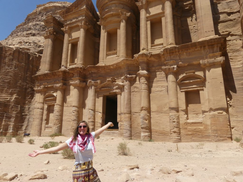 A young woman stands with arms outstreched in front of a building carved into a rock wall in Petra.