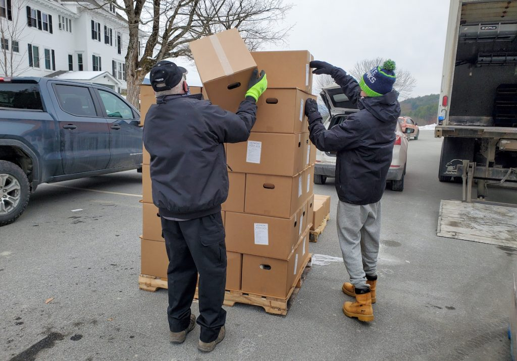 Volunteers stack boxes during a distribution event on the Vermont campus in January 2021.