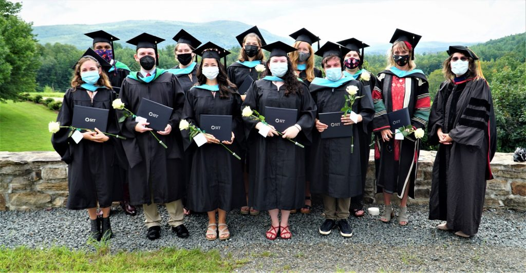 Eleven graduates in black gowns and black mortarboard caps with the SIT president in black gown and PhD cap. All are wearing protective masks.
