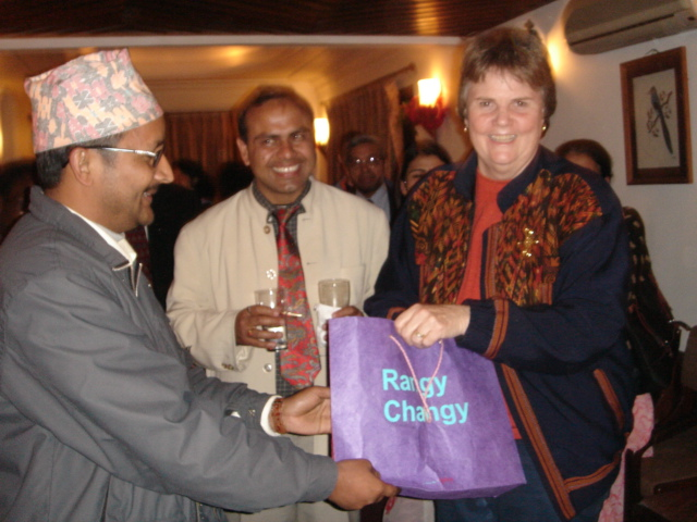 A woman smiles at the camera as a man hands her a gift bag.