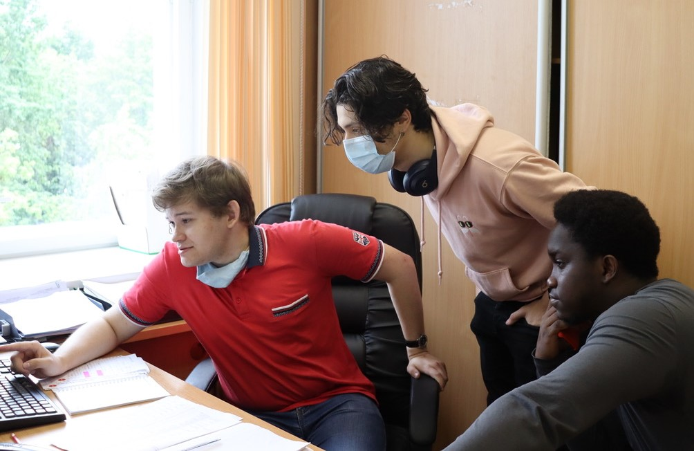 Three men, one wearing a surgical mask, look at a computer screen.