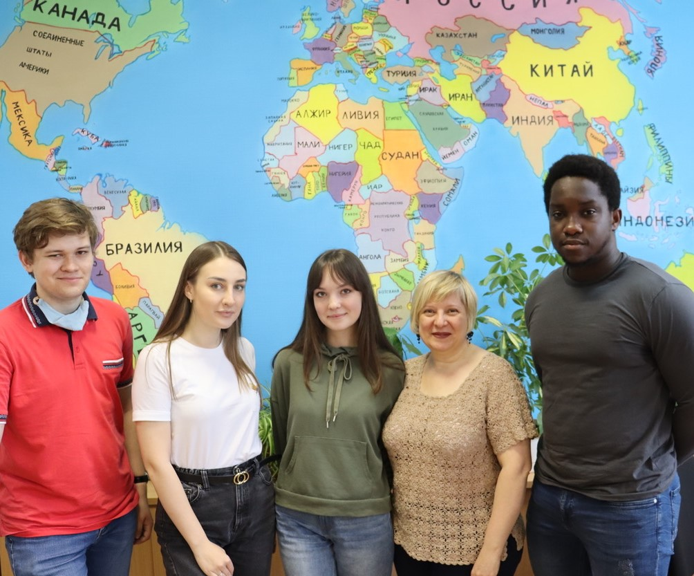 Two men and three women stand in front of a world map in Russia.
