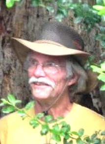 A man with a gray mustache, wearing a brimmed hat and glasses