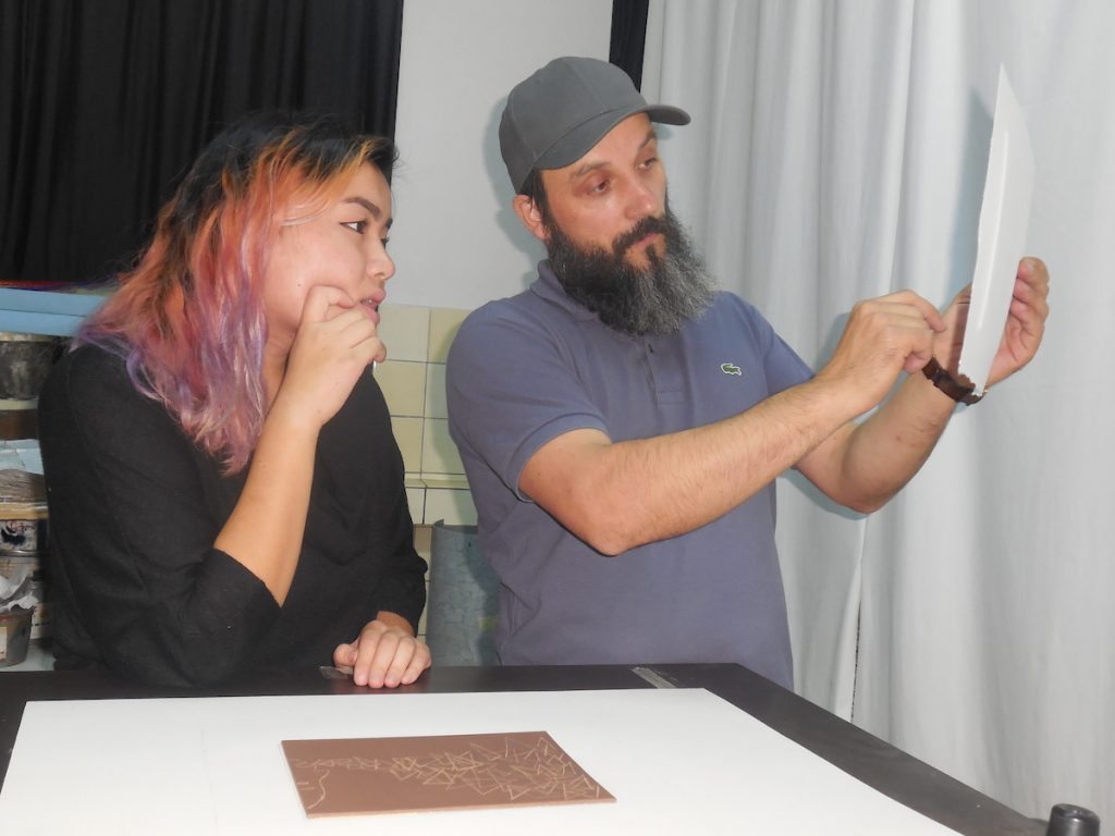 A female student gazes at a print  held by a man with a beard.