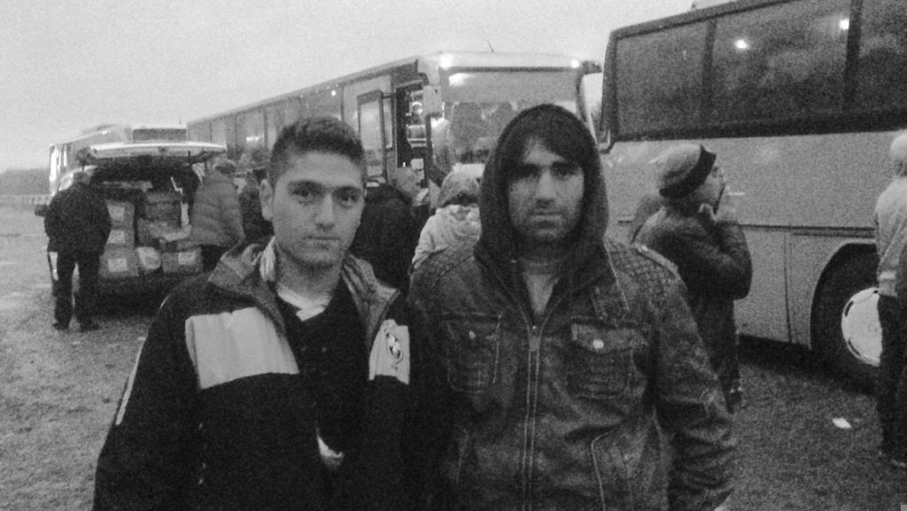 A black and white photo of two Afghan refugees in coats standing near buses in Serbia.