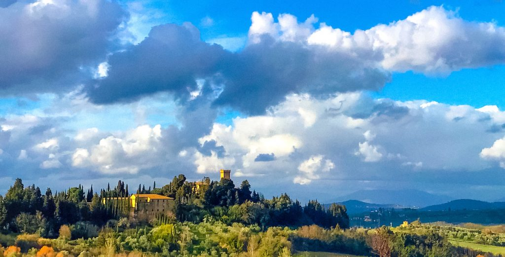 An Italian field and villa atop a hill, against blue skies with white clouds