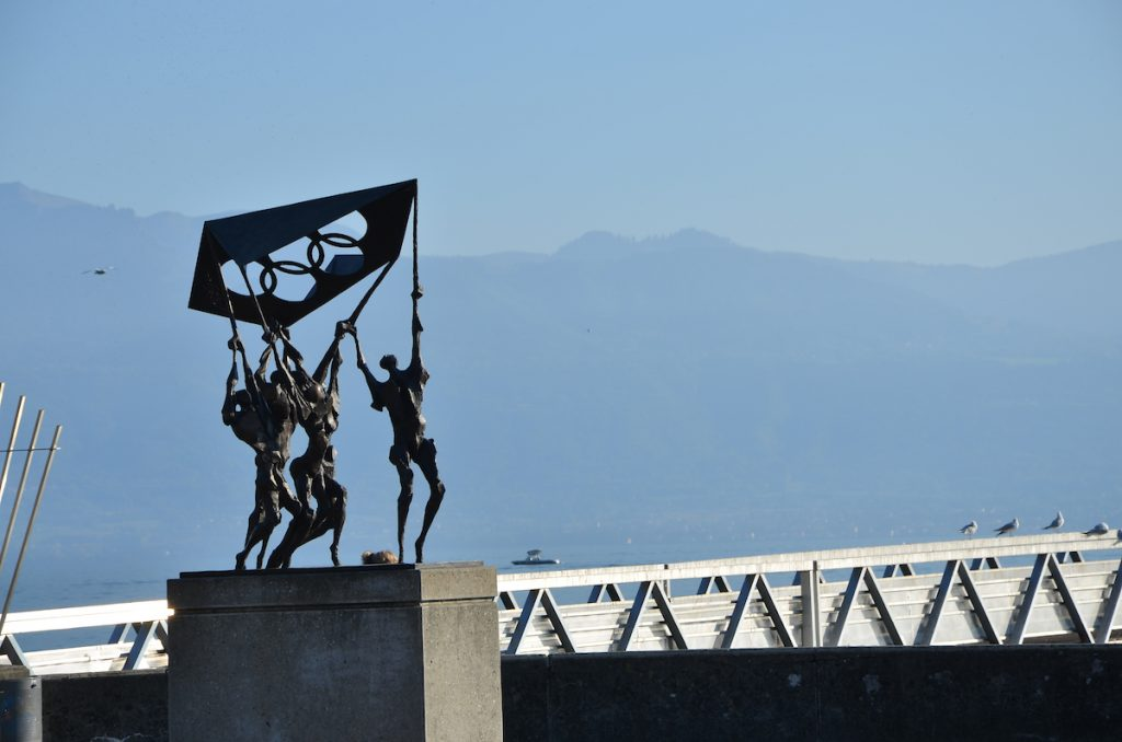 A modern metal status of tall humans holding a flag. In the background is a mountain and a bridge.