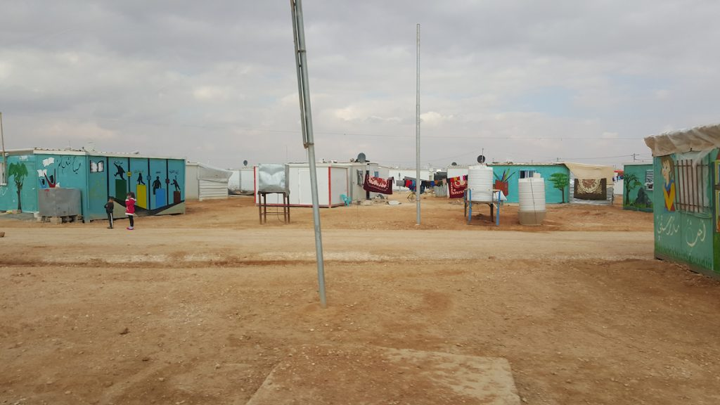 Small blue and white buildings, some with canvas tarps attached, on a dry, flat landscape.