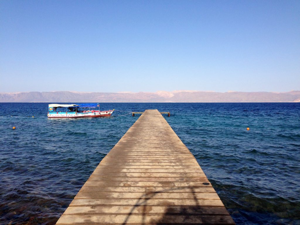 A wooden dock extends into a lake where there is a blue and red platform boat. Desert hills are in the background.