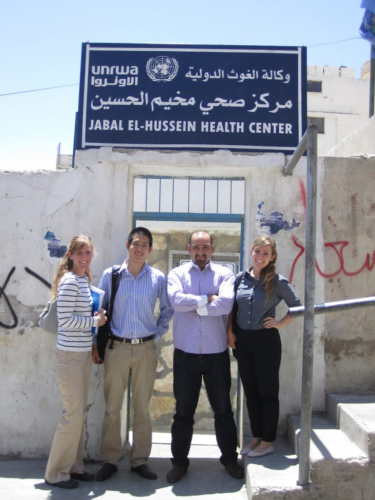 """Three students stand with a male doctor in front of a doorway. The sign above says """"Jabal El-Hussein Health Center."""""""