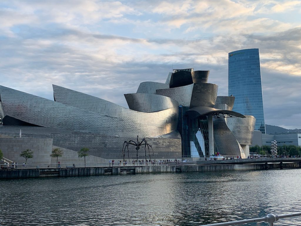 Modern, nonlinear architecture and a statue of a spider on a river bank in Bilbao, Spain.